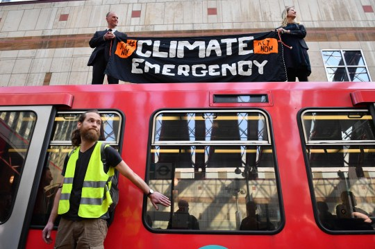 Climate change protestors, one of whom (L) has glued his hand to a window and two others who climbed atop a DLR train at Canary wharf station on the third day of an environmental protest by the Extinction Rebellion group, in London on April 17, 2019. - Nearly 300 people have been arrested in ongoing climate change protests in London that brought parts of the British capital to a standstill, police said Tuesday. (Photo by Daniel LEAL-OLIVAS / AFP)DANIEL LEAL-OLIVAS/AFP/Getty Images