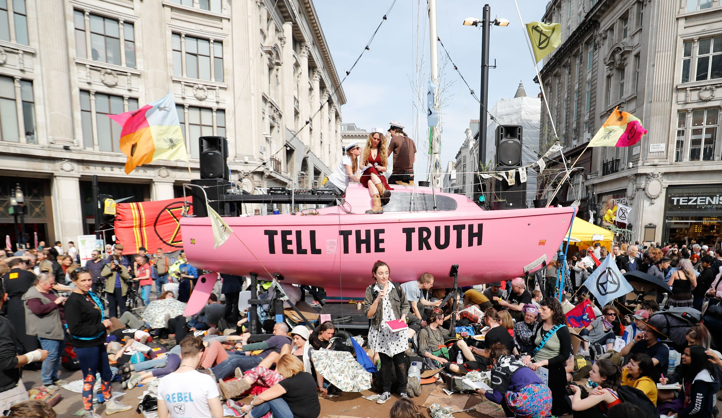 "TOPSHOT - Climate change activists listen to speeches at their encampment blocking the road junction at Oxford Circus in the busy shopping district in central London on April 18, 2019 during the fourth day of an environmental protest by the Extinction Rebellion group. - London commuters faced further disruption on Thursday as climate change protests continued to bring parts of the British capital to a standstill, leading to over 300 arrests. Demonstrators began blocking off a bridge and major central road junctions on April 15 at the start of a civil disobedience campaign calling for governments to declare an ecological emergency over climate change, to reduce greenhouse gas emissions to zero by 2025, halt biodiversity loss and be led by new ""citizens' assemblies on climate and ecological justice"". (Photo by Tolga AKMEN / AFP)TOLGA AKMEN/AFP/Getty Images"