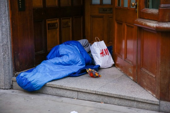 STOCK IMAGE LONDON, UNITED KINGDOM - 2018/12/21: A homeless man is seen sleeping on London's Oxford Street while covering his face with H&M shopping bag. On 18 December, Gyula Remes from Hungary died after choking on his own vomit outside the Houses of Parliament. According to official statistics published by the Office for National Statistics, 597 homeless people died in England and Wales in 2017. (Photo by Dinendra Haria/SOPA Images/LightRocket via Getty Images)
