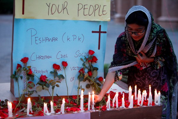 A Christian woman lights a candle at a vigil for the for the victims of bomb explosions in churches and hotels in Sri Lanka, in Peshawar, Pakistan, Sunday, April 21, 2019. (AP Photo/Mohammad Sajjad)