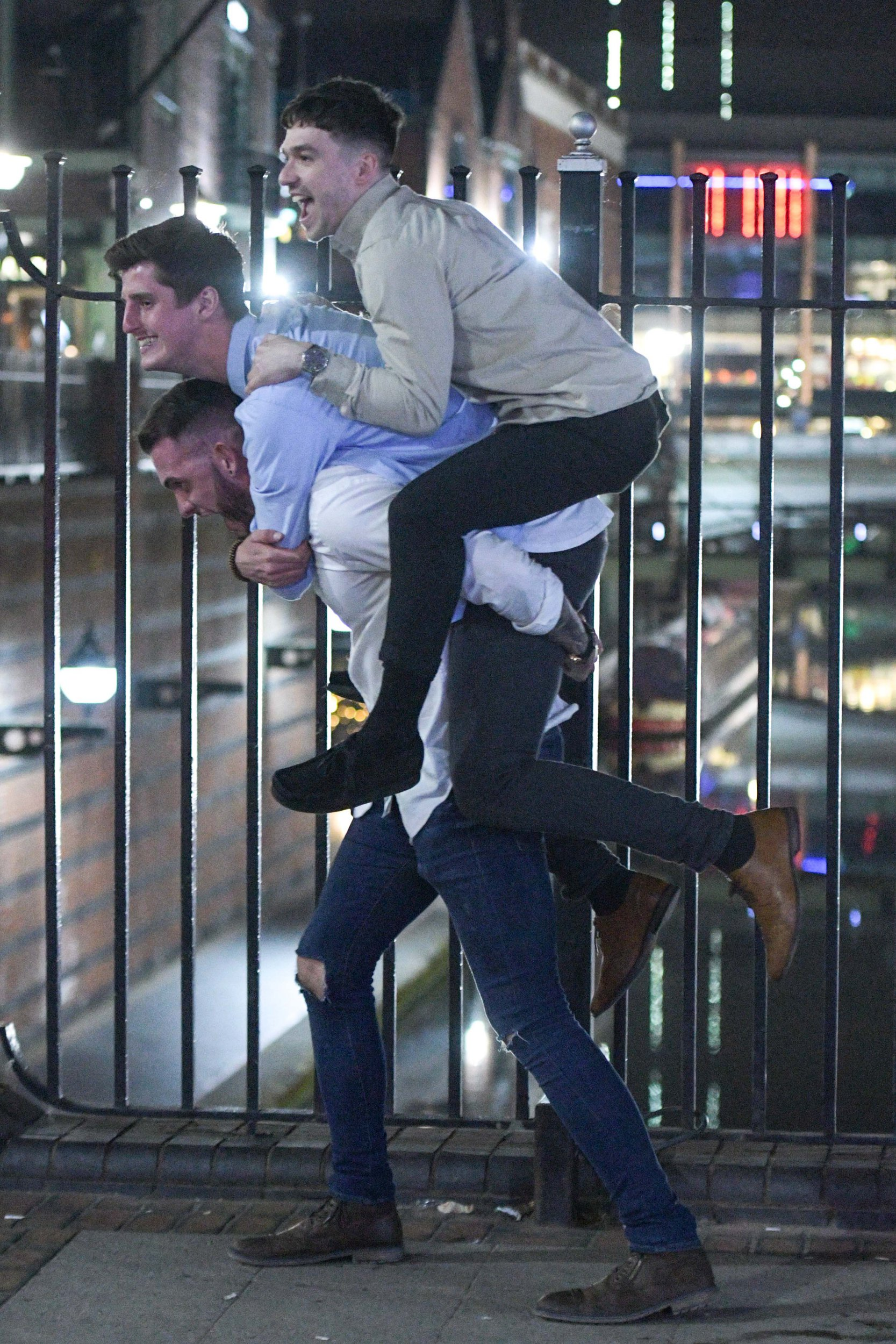 Pic by Michael Scott/Caters News - (PICTURED: An impressive triple person totem pole is achieved by 3 mates as they do a 3-person piggyback on Broad Street in Birmingham on the evening of Easter Sunday through to Bank Holiday Monday. Pic taken: 22/04/2019) - Birmingham partygoers ventured out for one last eventful night on the tiles as the Easter Bank Holiday brought the last party night in with the ability to sleep it off on Bank Holiday Monday. Ladies took advantage of the hot weather to wear a variety of minidresses. Some of the men got a little too rowdy and ended up being led away in handcuffs by police officers who were out in force on the evening of Easter Sunday through to Bank Holiday Monday. Some clubbers were a little worse for wear, one girl had to take a rest in the middle of the pavement after hanging off her mate who tried to flag a taxi down to take them home. Three lads created an impressive human totem pole by successfully pulling off a triple piggyback, and their faces showed the achievement. One man appeared to have an injury to his head whilst he talked to his mate and a girl tried to stop a friend from inhaling hippy crack (nitrous oxide) through a pink balloon. ENDS