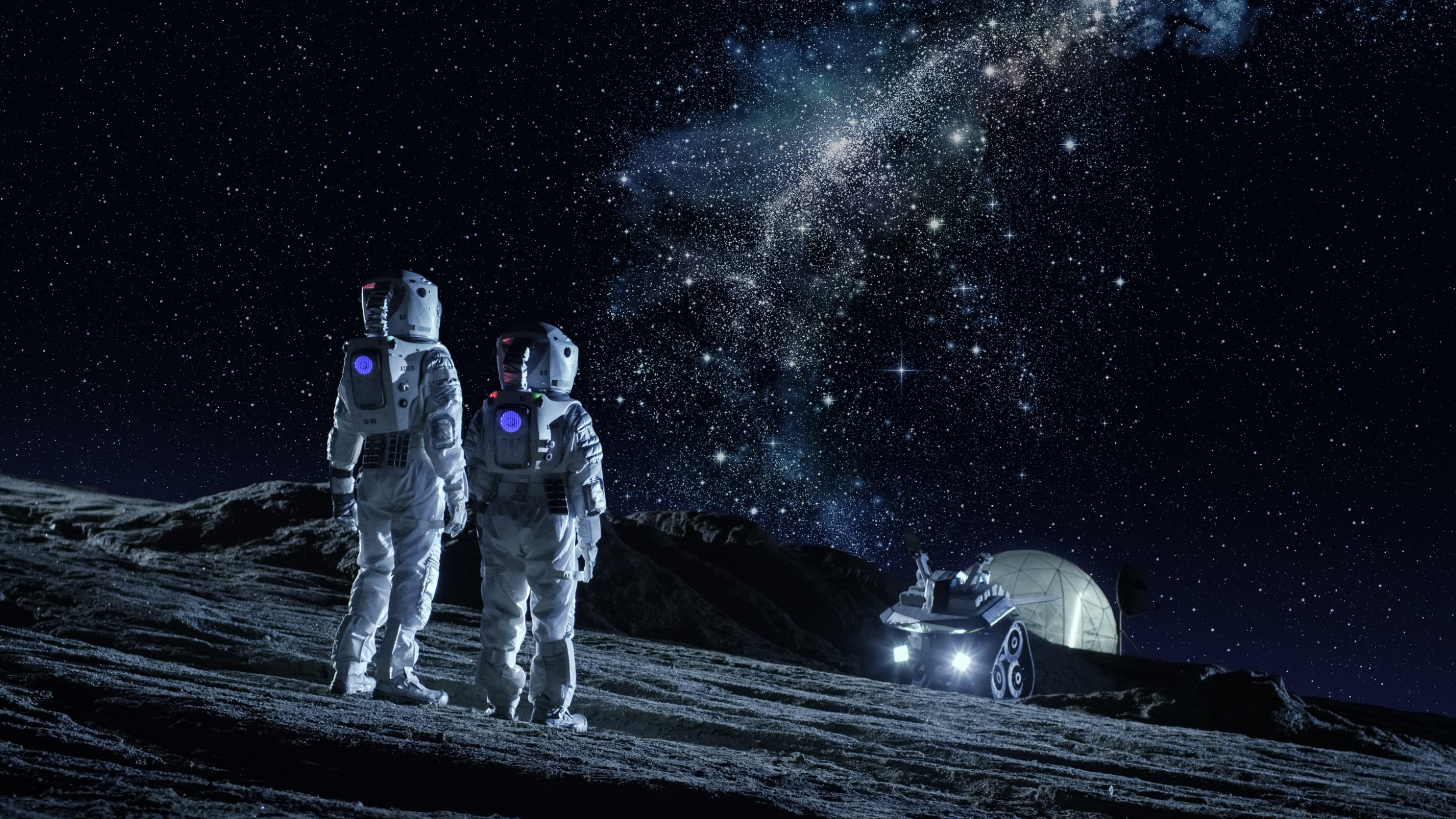 Two Astronauts in Space Suits Stand on a Planet and Looking during a The Milky Way Galaxy. In a Background Lunar Base with Geodesic Dome. Moon Colonization and Space Travel Concept.