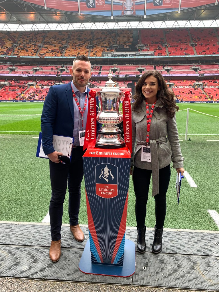 Kris Temple at Wembley Stadium during the FA Cup semi-final with co-host Kenzie Benali, posing with the trophy