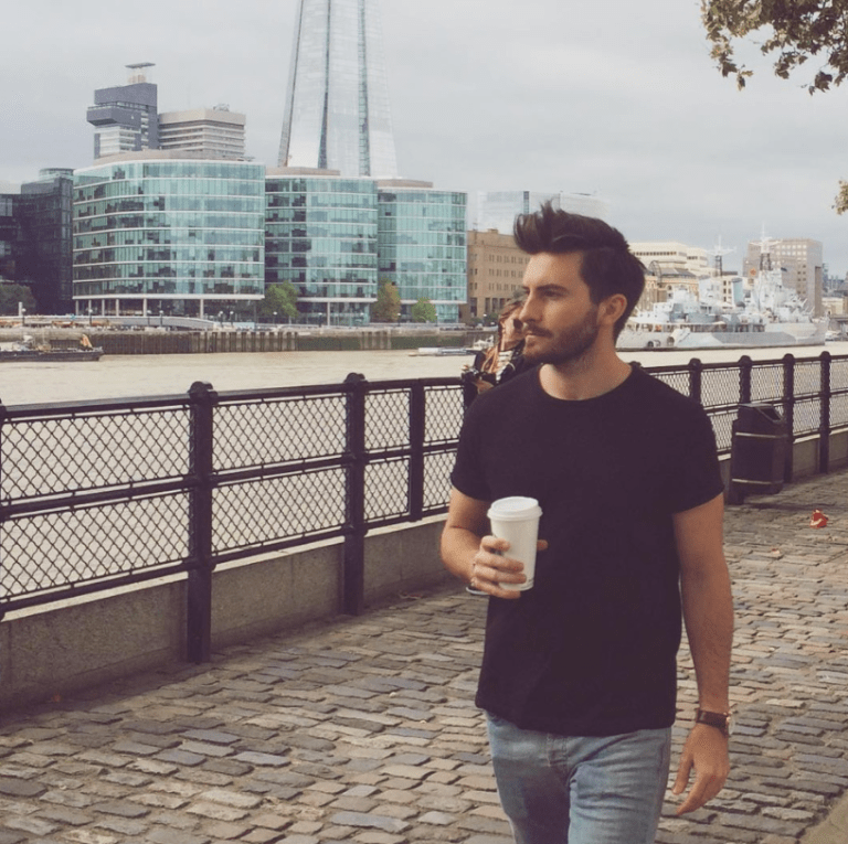A man walks besides the Thames in London carrying a coffee cup