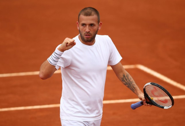 Dan Evans pumps his fist while playing on the clay