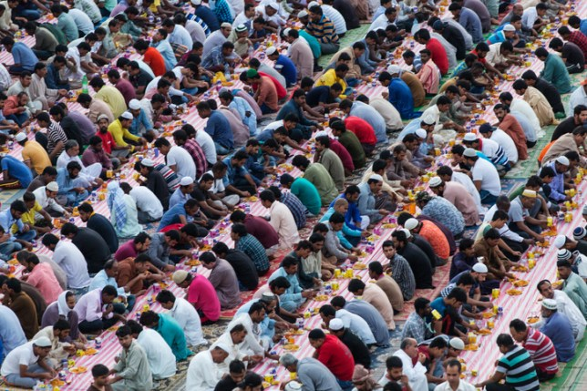 a large group of muslims breaking their ramadan fast with iftar