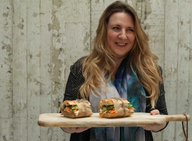 Food writer Helen Graves holding a wooden board with two sandwiches on it