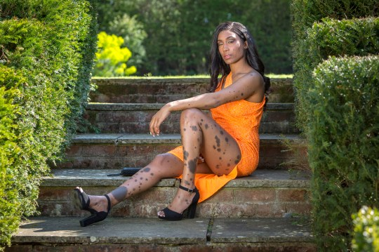 Cheryl Shaw, 34, poses on a set of stairs in a bright orange dress