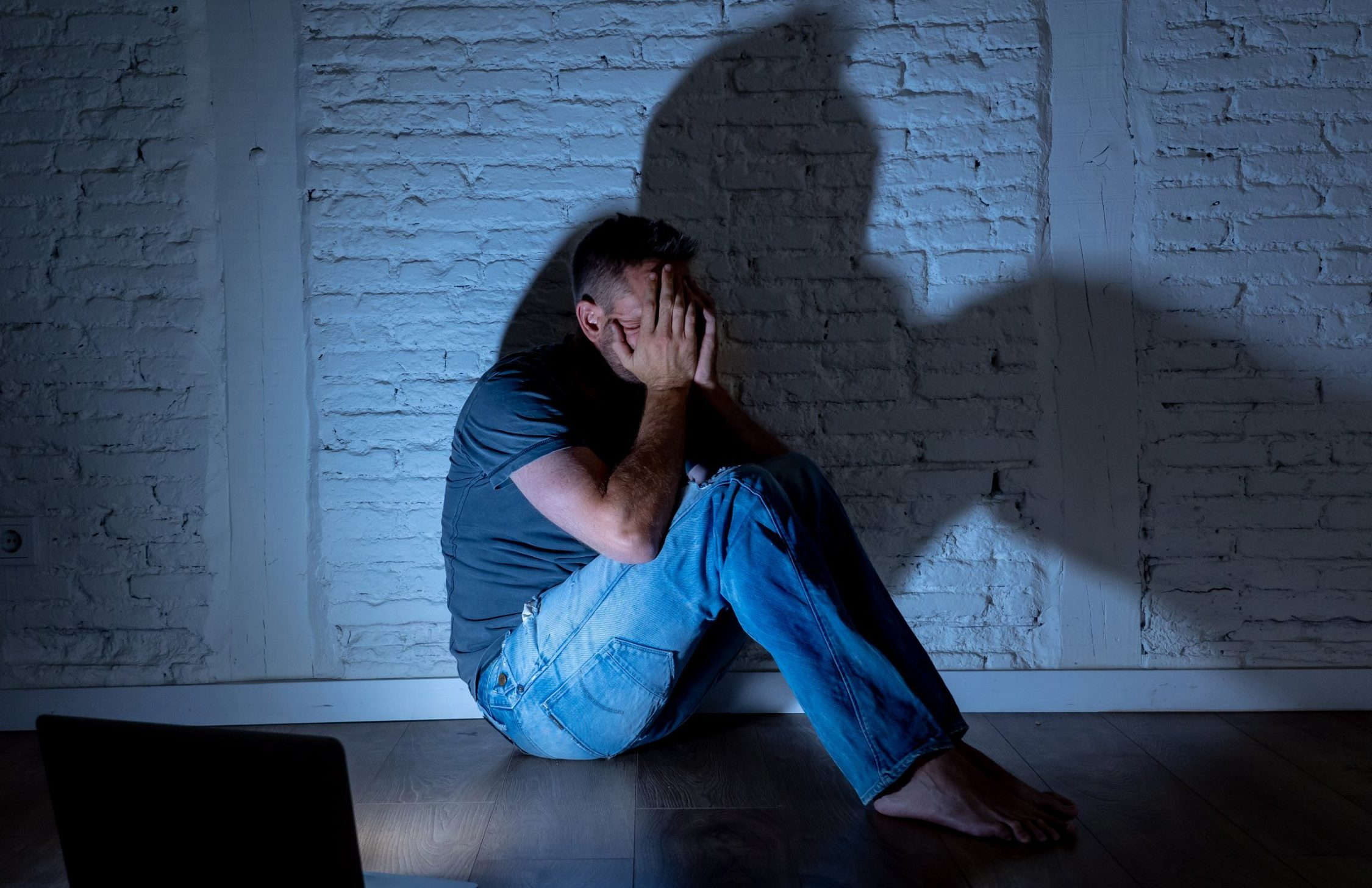 Severely distraught young men with laptop suffering cyberbullying and harassment being online abused by stalker or gossip feeling desperate and humiliated in cyber bullying and social media concept.