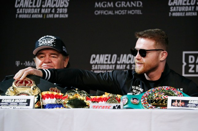 Canelo Alvarez, right, adjusts his belts during a news conference for a middleweight title boxing match against Daniel Jacobs, Wednesday, May 1, 2019, in Las Vegas. The two are scheduled to fight Saturday in Las Vegas. (AP Photo/John Locher)