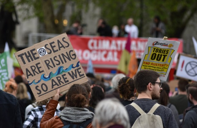 """LONDON, ENGLAND - MAY 01: Protesters hold a placard saying """"The seas are rising, so are we"""" during a Climate emergency protest in Parliament Square outside the Houses of Parliament on May 01, 2019 in London, England. The protest was organized by the Trade Union Group, Extinction Rebellion, School Strikes Against Climate Change and Momentum to campaign against climate change. The protest came on the evening that MPs passed a motion to make the UK parliament the first in the world to declare an environment and climate emergency. (Photo by John Keeble/Getty Images)"""