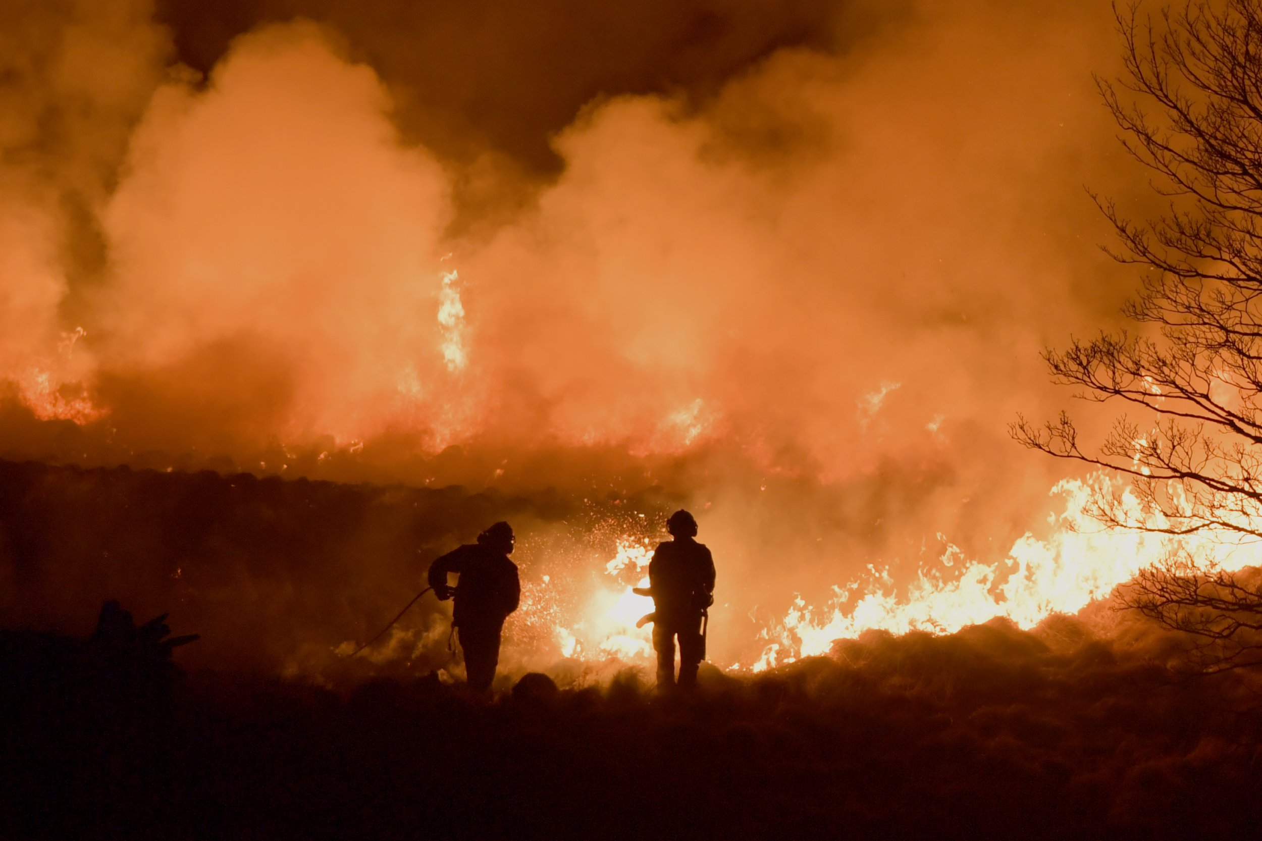 Firefighters tackle a large wildfire on Saddleworth Moor on February 26, 2019