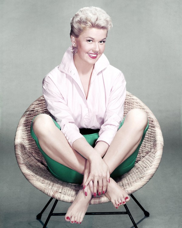 American actress and singer Doris Day sits cross-legged and barefoot in a rattan chair, circa 1955. (Photo by Silver Screen Collection/Getty Images)