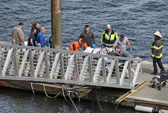 Emergency response crews transport an injured passenger to an ambulance at the George Inlet Lodge docks, Monday, May 13, 2019, in Ketchikan, Alaska. The passenger was from one of two float planes reported down in George Inlet early Monday afternoon and was dropped off by a U.S. Coast Guard 45-foot response boat. (Dustin Safranek/Ketchikan Daily News via AP)