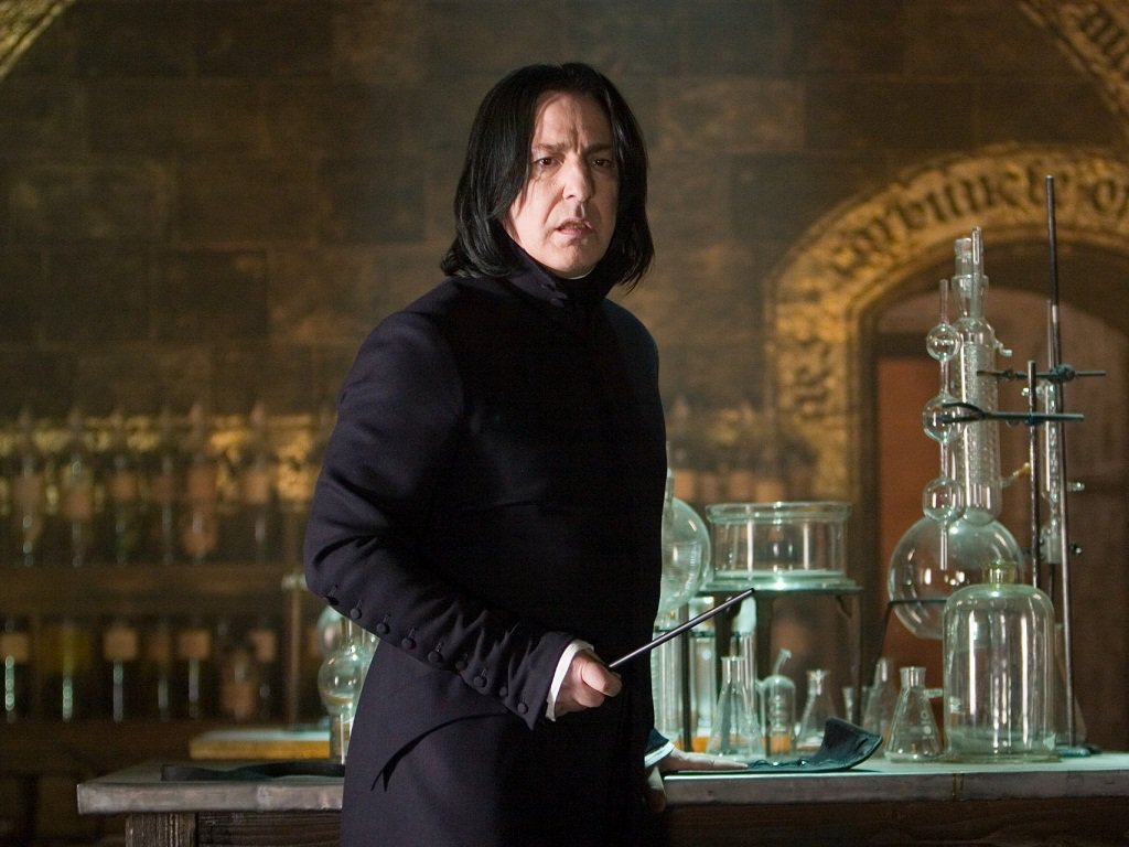 Professor Snape (the late actor Alan Rickman) in a scene from Harry Potter, holding a wand and staring into the distance
