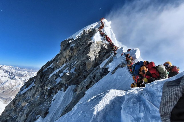 Heavy traffic of mountain climbers lining up to stand at the summit of Mount Everest