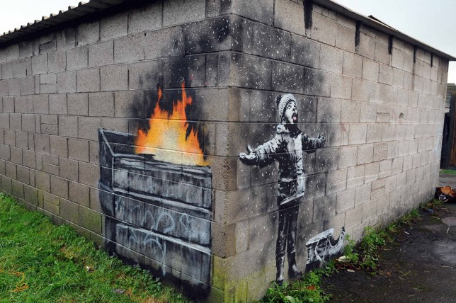 A Banksy mural weighing 4.5 tonnes is set to be cut out of a garage today(Tues) and moved across a town. The piece of art caused a stir when it was painted onto the corner wall of a garage in the dead of night. It shows a child standing under falling ash that appears as snow in a polluted steel town. Pictured here is the season's greetings Banksy mural ?? WALES NEWS SERVICE