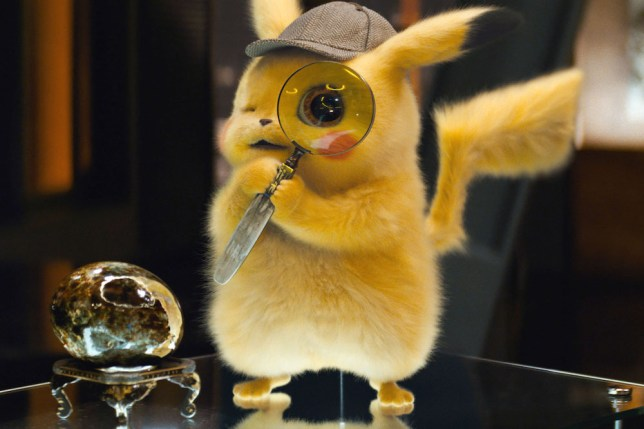 Pokemon Detective Pikachu holding up a magnifying glass while wearing a hat