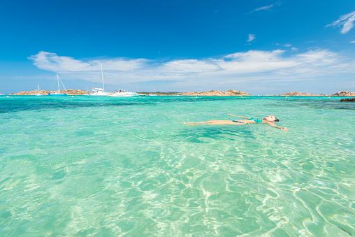 Une femme flotte dans l'eau au large de l'une des plages préservées de la Sardaigne
