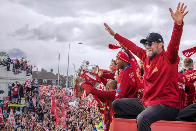 Jurgen Klopp and Liverpool players on top of their red bus celebrating their Champions League win with fans