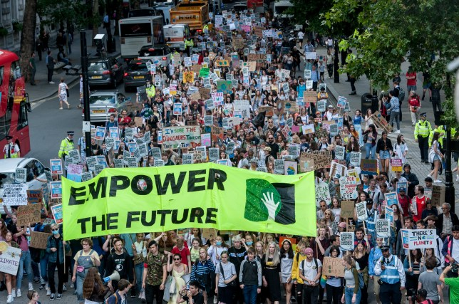 Students marching for climate change and holding up a sign that reads: 'Empower the future'