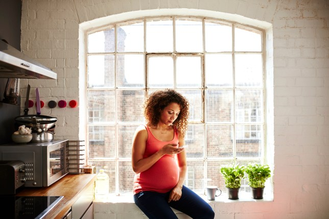 A pregnant woman sitting in a kitchen