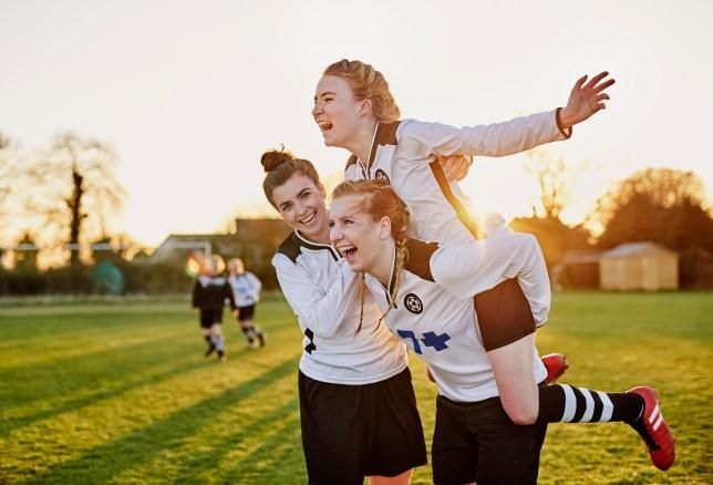 Female footballers celebrating goal