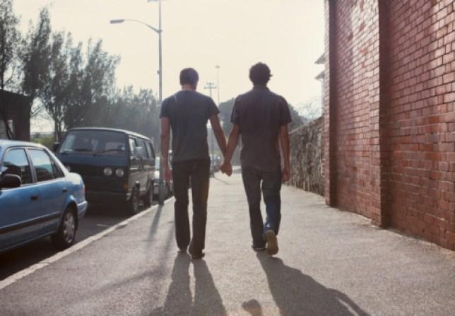Two men walk down street holding hands