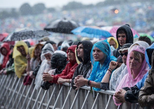 Crowd wearing rain coats and leaning on barrier at Glastonbury Festival at Worthy Farm
