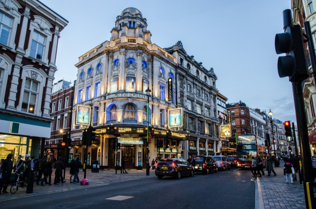 London, England - May 3, 2016: Evening at Shaftesbury Avenue in London, Soho, where we are on the street from the Gielgud Theater and other theaters around with people and cars. Beautiful architectural building lights up. This is spring.