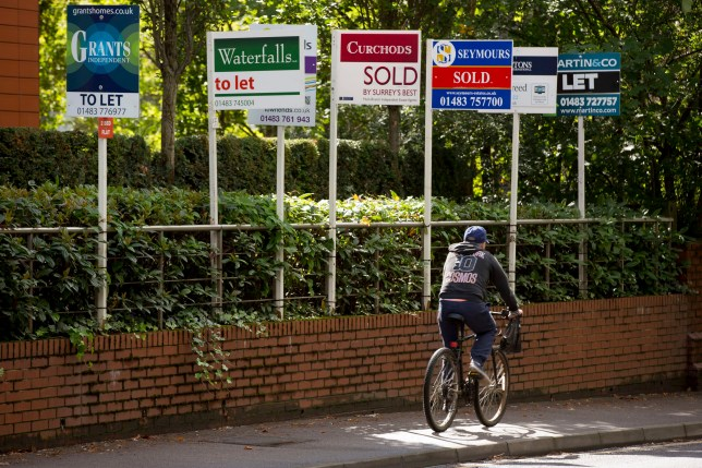 """A cyclist rides past estate agents' """"Sold,"""" """"Let By,"""" and """"To Let"""" signs outside a residential property"""