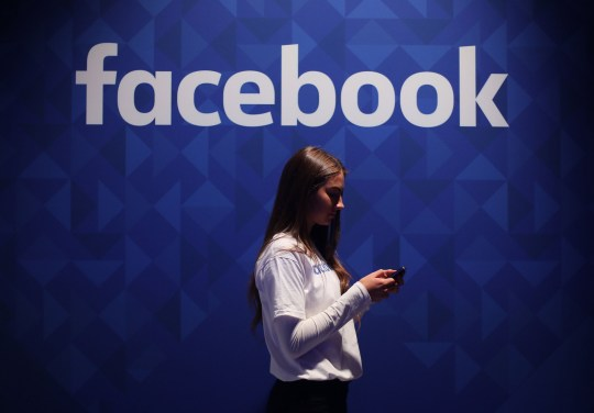 File photo dated 03/11/15 of a woman using her phone under a Facebook logo. A former classmate of Mark Zuckergerg has claimed Facebook bosses have lost control of the social network and is unlikely to regain it. PRESS ASSOCIATION Photo. Issue date: Wednesday June 5, 2019. Aaron Greenspan, who knew Mr Zuckerberg during their time at Harvard College in 2003 and 2004, launched a scathing attack on the chief executive's ability to lead and reiterated previous accusations of fraud. See PA story TECHNOLOGY Facebook. Photo credit should read: Niall Carson/PA Wire