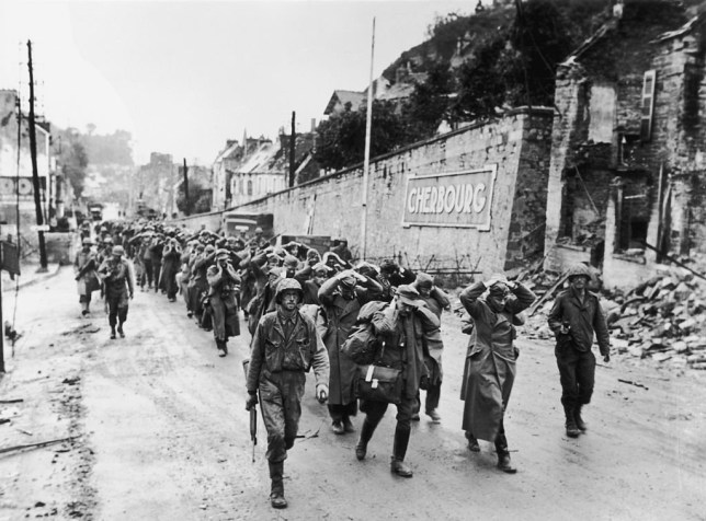 June 1944: German soldiers are seen here being marched through the streets of Cherbourg, France, after the city was liberated by the Americans. (Photo by Three Lions/Getty Images)