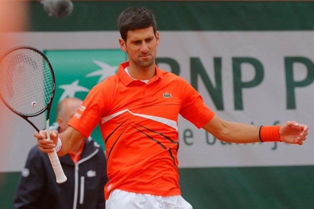 Serbia's Novak Djokovic gestures as wind blows over center court prior to a rain delay of his semifinal match of the French Open tennis tournament against Austria's Dominic Thiem at the Roland Garros stadium in Paris, Friday, June 7, 2019. (AP Photo/Michel Euler)