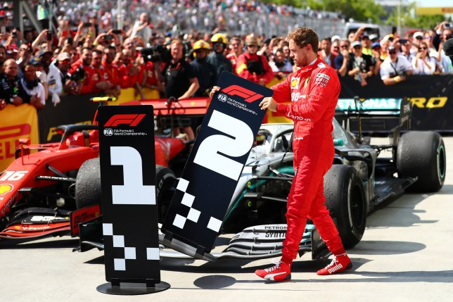 Second placed Sebastian Vettel of Germany and Ferrari swaps the number boards at parc ferme during the F1 Grand Prix of Canada
