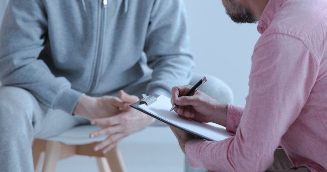 Psychologist interviewing man during therapy