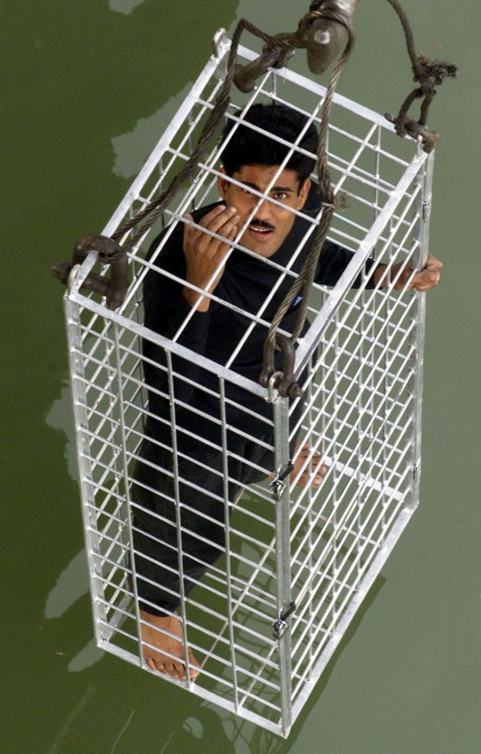 Caged Indian escape artist Chanchal Lahiri is lowered into the Hooghly river from Calcutta's Howrah Bridge February 24, 2002. Lahiri escaped from the locked cage about 15 seconds after it was submerged. REUTERS/Jayanta Shaw JS/JD - RP3DRHYOKUAA