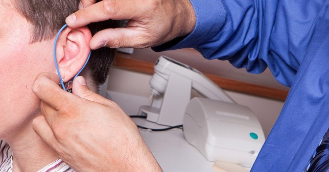 Healthcare professional performing an ear exam on a patient. Please view all images from this series along with other