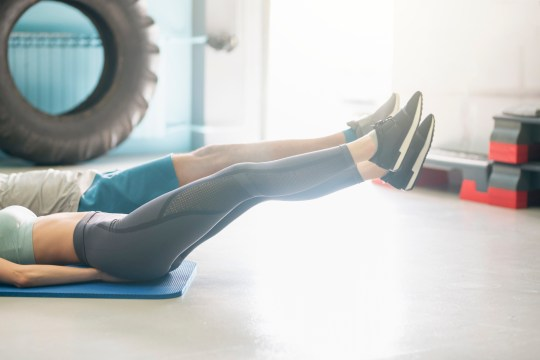 The bottom halves of a man and woman lying on a mat in the gym with their legs raised