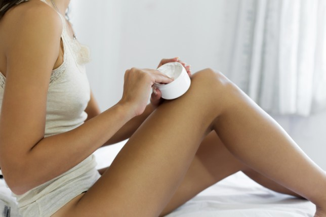 Young woman holding lotion