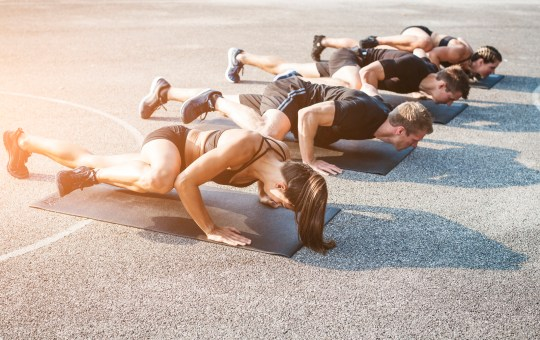 Group of people doing spiderman push-ups on concrete