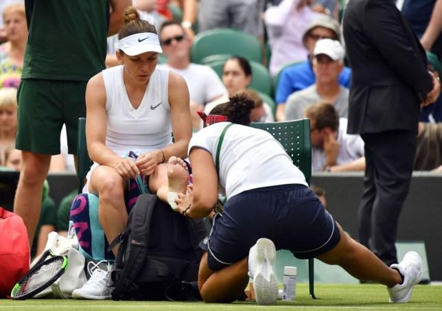 Simona Halep receives treatment after a nasty fall at Wimbledon