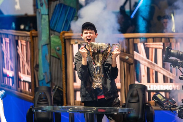 """Kyle """"Bugha"""" Giersdorf lifting the Fortnite World Cup trophy at Arthur Ashe Stadium"""