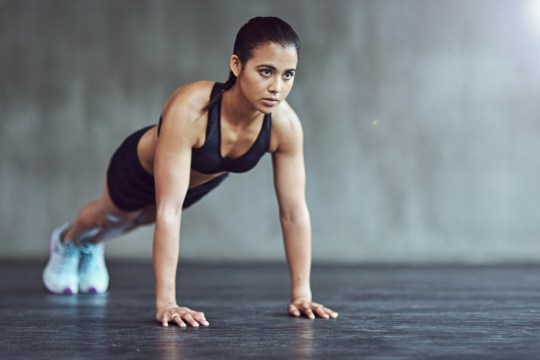 Woman doing a plank with straight arms on a gym floor