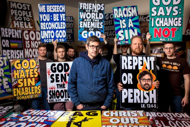Louis Theroux standing next to members of the Westboro Baptist Church holding picket signs