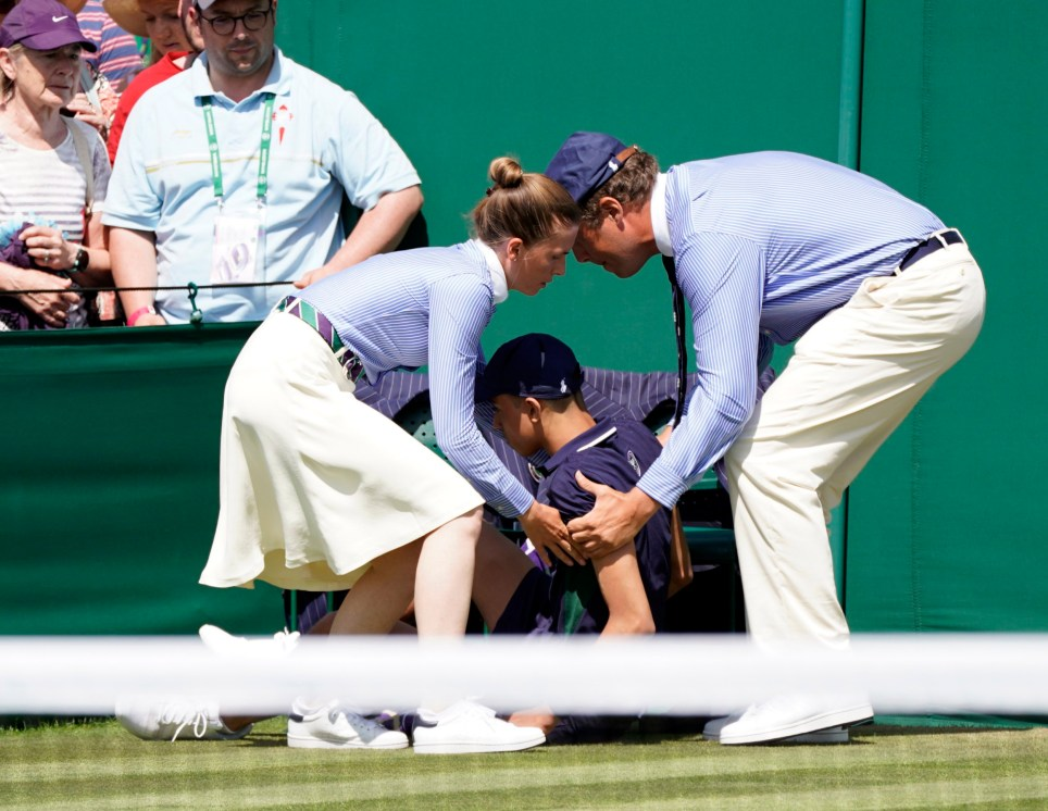 epa07686918 Lines staff assist a ballboy who fainted in the heat on an outside court in the first round of the Wimbledon Championships at the All England Lawn Tennis Club, in London, Britain, 01 July 2019. EPA/NIC BOTHMA EDITORIAL USE ONLY/NO COMMERCIAL SALES