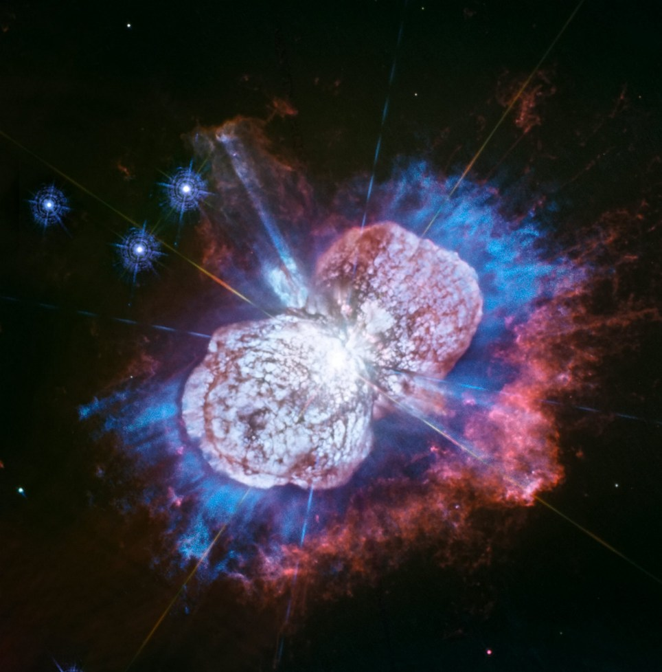 *** PICTURE CREDIT MUST BE USED AS SHOWN*** *** CREDIT - NASA, ESA, N. Smith (University of Arizona, Tucson), and J. Morse (BoldlyGo Institute, New York) /SWNS.COM *** The Eta Carinae nebula's cosmic firewors in ultraviolet. See National News story NNstars. From 7,500 light years away, hot beams of red, white and blue gases can be seen shooting from, Eta Carinae, one of the Milky Way???s most ???petulant??? stars in this new image from NASA's Hubble Space Telescope. They are the latest shots of a 170 year-long firework show which started with the star's ???Great Eruption??? in the 1840s.The picture, taken by Nasa's Hubble???s Wide Field Camera 3, reveals the ultraviolet-light glow of magnesium embedded in warm gas (shown in blue), which could help scientists better understand the unique star's unpredictable behaviour. The largest member of a double-star system, Eta Carinae weighs 150 times our sun's mass.