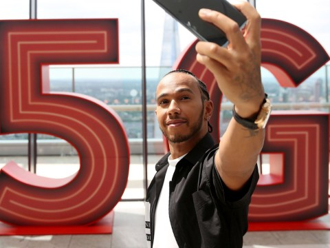 Lewis Hamilton looks groomed as he turns on Vodafone's new 5G network after his curly-haired selfie this week