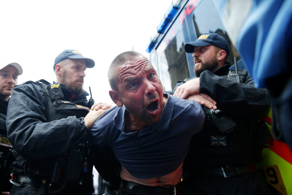 LONDON , UNITED KINGDOM - JULY 11: A protester is detained by police after scuffles broke out outside parliament during a demonstration following the sentencing of British far-right activist and former leader and founder of English Defence League (EDL), Tommy Robinson - whose real name is Stephen Yaxley-Lennon, at the Old Bailey on July 11, 2019 in London, England. Far-right activist Tommy Robinson has been sentenced to nine months in prison for contempt of court. He was found guilty of filming defendants accused of child sex offences outside Leeds Crown Court and live-streaming the footage on Facebook in May, 2018. (Photo by Luke Dray/Getty Images)