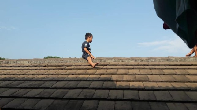 Pic shows: The little boy climbed on the roof and refused to come down to be circumcised. This was the hilarious scene when a small boy climbed onto the roof of a building and refused to come down after his parents took him to a clinic to be circumcised.